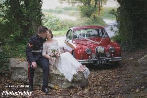 A newly wed couple and a vintage red car on their wedding day.