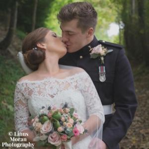 An image of a Forces couple kissing on their wedding day.
